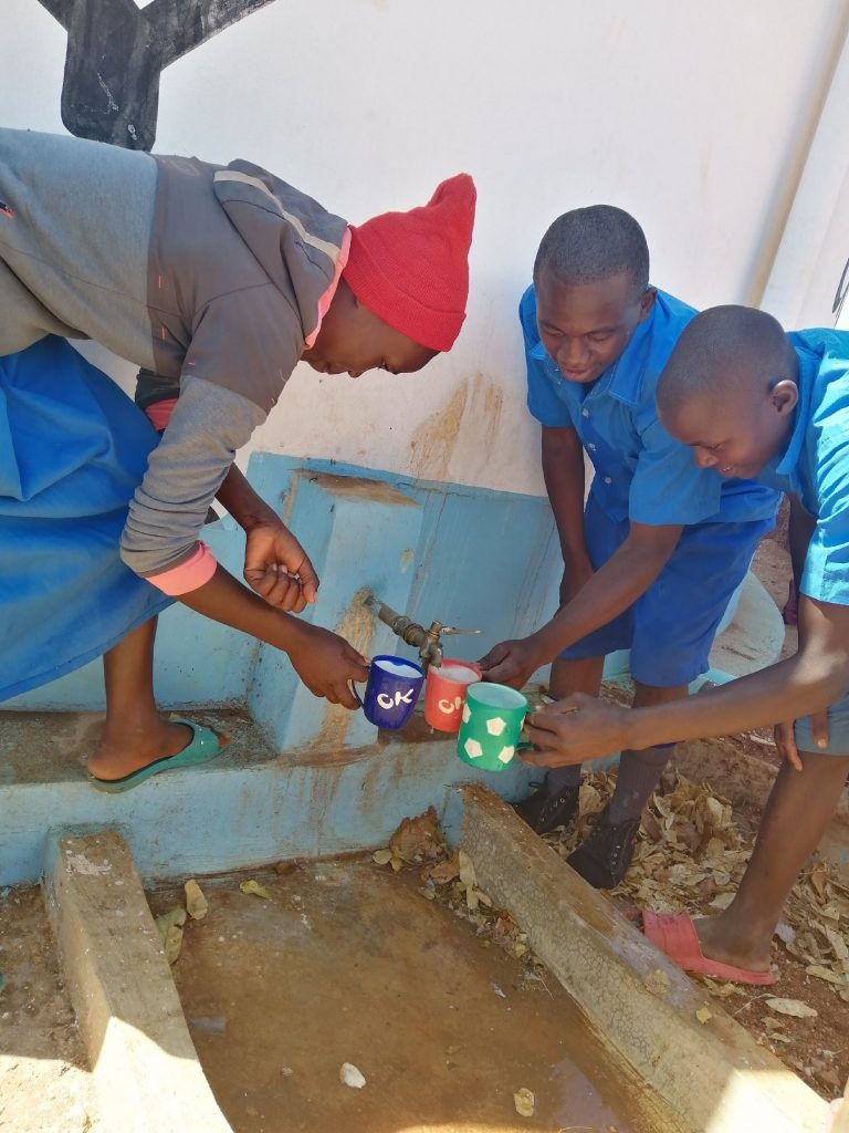 The Water Project : kenya20354-kids-drink-water-from-the-tank