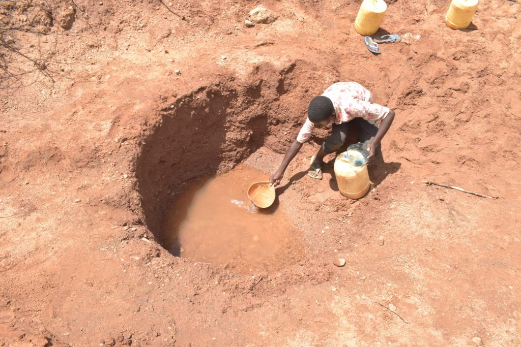 The Water Project : kenya21456-collecting-water-at-the-scoop-hole