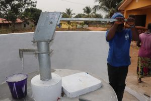 The Water Project:  Staff Collects Water After Installing Pump