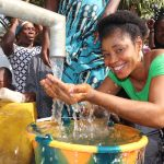 The Water Project: Lungi, New York, Robis, #7 Masata Lane -  Woman Drinking Pure And Clean Water