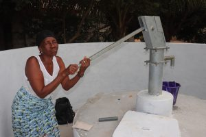 The Water Project:  Woman Collects Water After Pump Installation