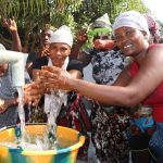 The Water Project: Lungi, New York, Robis, #7 Masata Lane -  Women Splashing Clean Water