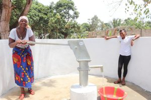 The Water Project:  Woman Joufully Collecting Water With Her Child
