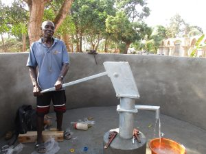 The Water Project:  Community Member Collecting Water After Pump Installation