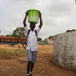 The Water Project: Kankalay Primary and Secondary School -  Student Carrying Water