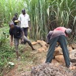 The Water Project: Musango Commnuity, Wabuti Spring -  Backfilling With Large Rocks