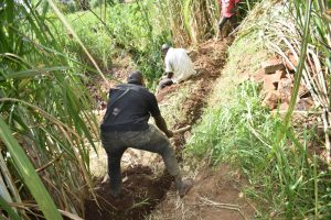The Water Project:  Constructing Cutoff Drainage Channel Above Spring