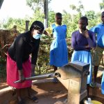 The Water Project: Ibokolo Primary School -  Teacher Helps Pupils Fetch Water