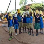 The Water Project: Ibokolo Primary School -  Pupils Carrying Water