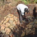 The Water Project: Musango Commnuity, Wabuti Spring -  Laying Stone Pitching