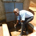 The Water Project: Immaculate Heart Secondary School -  Fredrick Getting A Drink From The Rain Tank