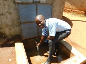 The Water Project:  Fredrick Getting A Drink From The Rain Tank