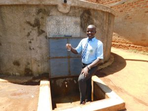 The Water Project:  Fredrick Holds Up A Glass Of Clean Water From The Rain Tank