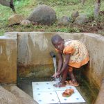 The Water Project: Musango Community, Mwichinga Spring -  Mitchel Rinsing Off At The Spring