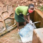The Water Project: Mutao Community, Shimenga Spring -  Loreen Fetching Water