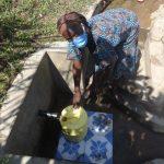 The Water Project: Eshikhugula Community, Shaban Opuka Spring -  Madam Rebecca Fetching Water