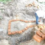 The Water Project: Shianda Township Community, Olingo Spring -  Construction Of The Headwall And Wing Walls
