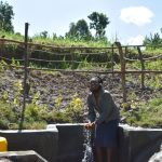 The Water Project: Machemo Community, Boaz Mukulo Spring -  Woman Splashing Water