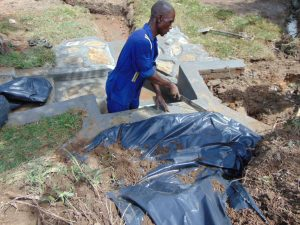 The Water Project:  Fitting The Tarp Over The Stones
