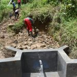 The Water Project: Mukhungula Community, Mulongo Spring -  Backfilling With Rocks As Water Begins To Flow