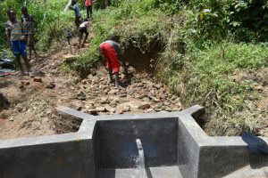 The Water Project:  Backfilling With Rocks As Water Begins To Flow