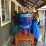 The Water Project: Ibokolo Primary School -  Adding Water To Filter For Storage