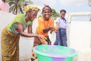 The Water Project:  Community Members Joyfullly Splashing Water