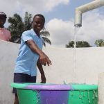 The Water Project: Sulaiman Memorial Academy Jr. Secondary School -  Student Pointing At Clean Water Flowing