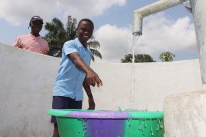 The Water Project:  Student Pointing At Clean Water Flowing