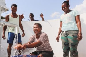 The Water Project:  Woman Happily Looking At Clean Water Flowing On Her Hands