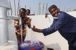 The Water Project:  Head Teacher And Supervisor Of School Splashing Water