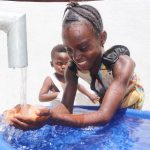 The Water Project: Lungi, Suctarr, #1 Kabbia Lane -  Kid Joyfully Looking At Clean Water Flowing