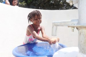 The Water Project:  Kid Joyfully Looking At Clean Water Flowing
