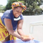 The Water Project: Lungi, Suctarr, #1 Kabbia Lane -  Woman Rejoicing For Clean Water Flowing