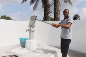 The Water Project:  Teacher Collecting Water After Installation