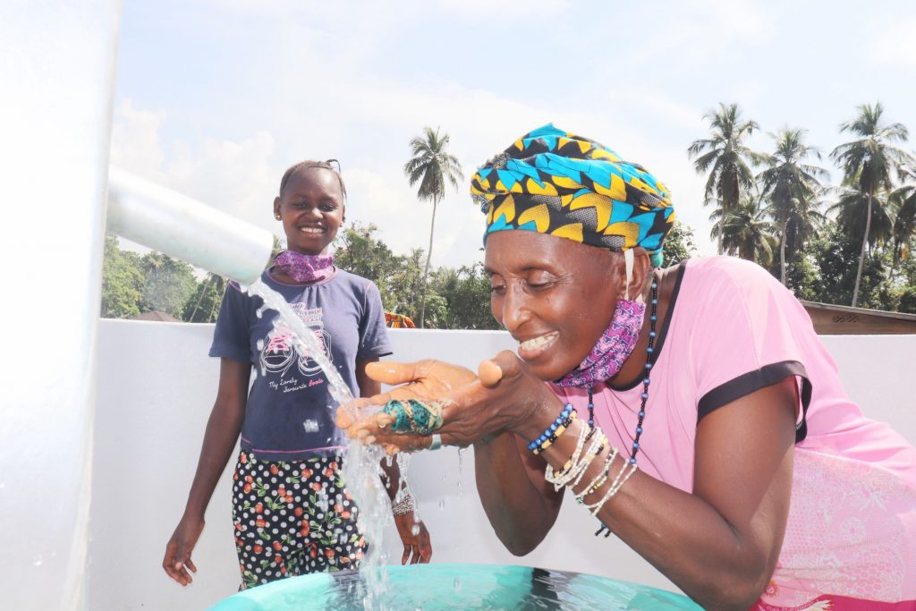 The Water Project : sierraleone20434-community-member-joyfully-looking-at-safe-drinking-water-flowing-2