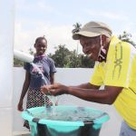 The Water Project: Lokomasama, Conteya Village -  Councilor Dixion Joyfully Looking At Clean Water Flowing