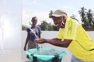 The Water Project:  Councilor Dixion Joyfully Looking At Clean Water Flowing