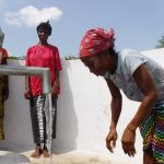 The Water Project: Lokomasama, Rotain Village -  Community Members Looking At Clean Water Flowing