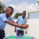 The Water Project: Sulaiman Memorial Academy Jr. Secondary School -  Student Joyfully Looking At Clean Water Flowing