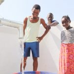 The Water Project: Lungi, Suctarr, #3 Lovell Lane -  Community Members Joyfully Looking At Clean Water Flowing