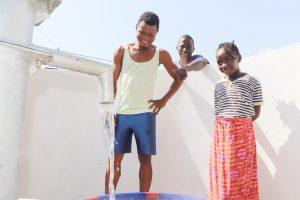 The Water Project:  Community Members Joyfully Looking At Clean Water Flowing