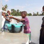 The Water Project: Lokomasama, Conteya Village -  Kid Joyfully Looking At Clean Water Flowing