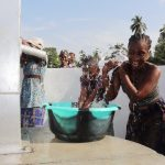 The Water Project: Lokomasama, Conteya Village -  Woman And Kid Splashing Water