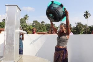 The Water Project:  Woman Happily Pouring Water On Herself