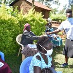 The Water Project: Musango Commnuity, Wabuti Spring -  Trainer Joyce Giving A Mask To A Participant