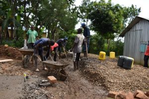 The Water Project:  Many Hands Help Mix Concrete