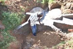 The Water Project:  Reinforcing Headwall With Clay For Better Collection