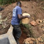 The Water Project: Mukhonje B Community, Peter Yakhama Spring -  Adding Clay Soil Behind Headwall