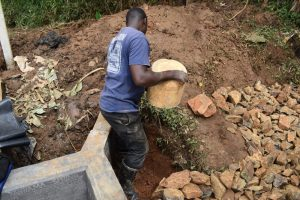 The Water Project:  Adding Clay Soil Behind Headwall